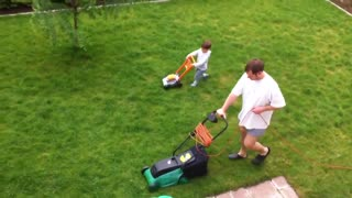 Father and son adorably mow the lawn together