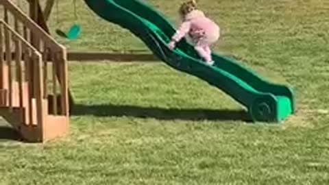Little girl keeps slipping while trying to climb up slide
