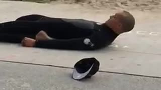 Guy surfer on beach stretching with legs folded back on sidewalk - Video