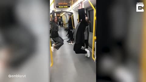 WOMAN TRYING TO HANG OFF UNDERGROUND TRAIN BAR FALLS BACKWARDS OUT OF THE CARRIAGE AS IT PULLS OUT OF STATION
