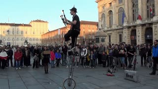 Street performer juggles torches while balancing on a unicycle