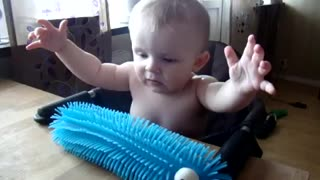 Baby scares himself by touching toy - Video