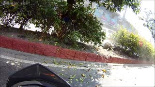 Car Swerves on Center Island Nearly Hitting a Motorcyclist - Video