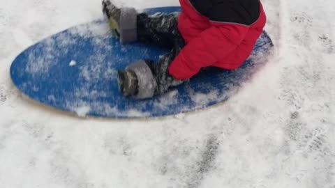 Baby flies down the hill on the snow