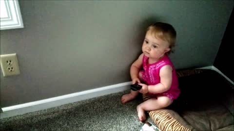 Toddler attempts to use TV remote