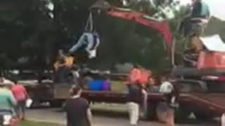 Guy strapped to excavator tosses candy during parade - Video