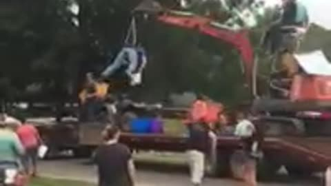Guy strapped to excavator tosses candy during parade