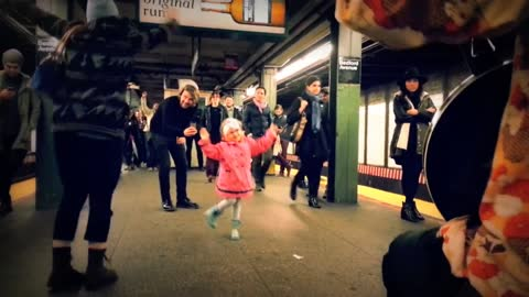 Little Girl Dances Along with Subway Performers