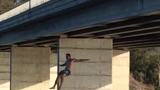 Shirtless man backflips off bridge and back flops in river