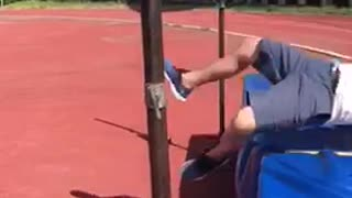 Guyrunning on track field tries to jump over pole fails - Video