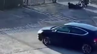 Security camera, guys turns out of a gate on motorcycle and falls over