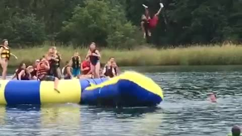 Dad man launches kid off of inflatable bean into water lake