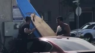 Two men put two surf boards through sunroof of red car