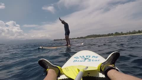 Guy paddle board handstand fail