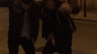 Two guys dance in the middle of the street at night  - Video