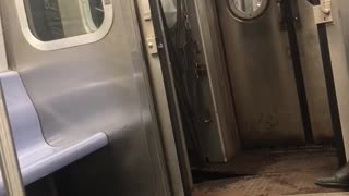 Man black jacket holding subway doors open while train moves - Video