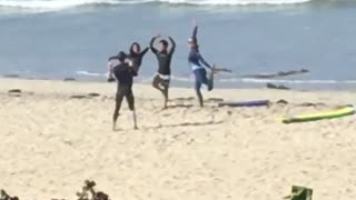 Girl sees three surfers on the beach posing for a picture  - Video