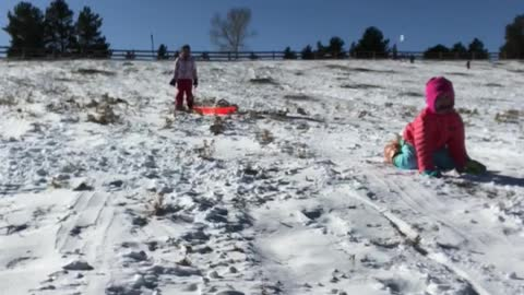 Mom on sled with little girl in pink gets dropped off in snow