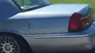 Small blue car tows large white boat down road - Video