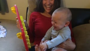 Baby laughs hysterically at 'Guess Who?' game - Video