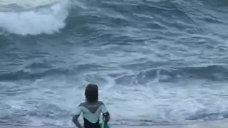 Girl black wet suit dancing on beach sand watching waves