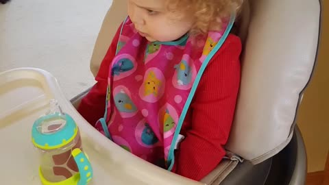 2-year old verbally expresses a range of emotions in her high chair