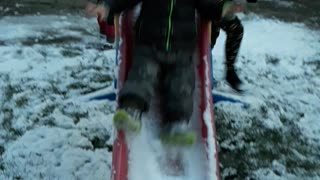 Baby slides down snow covered red slide and stairs at camera