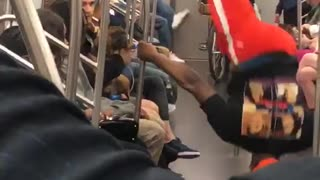 Brown french bulldog dancing on subway to music as guy in red dances