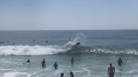 Little girl blue bathing suit gets knocked over by cute wave next to her friend