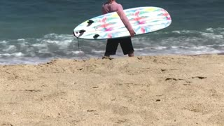 Guy in pink shirt carrying blue surf board