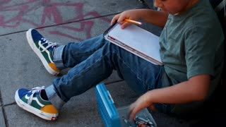 Boy Sitting While Coloring His Art Work