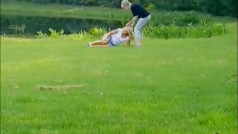 Dogs runs in grass to couple knocks over blonde lady in white