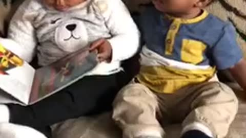 Big sister reads baby brother a story