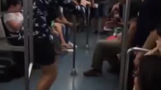 Guy blue button up shirt white shoes dancing on subway train