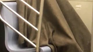 Guy sleeps under brown blanket in corner of subway - Video