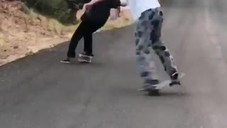 Two guys skateboard one falls on street