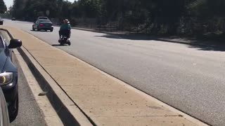 Blissfully Unaware Senior Rides Scooter on Highway