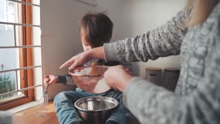 A small child helps his mother with cooking