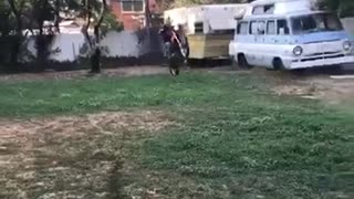 Man in black shirt falls off red dirt bike next to house
