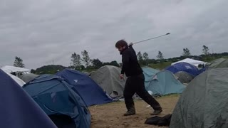 Guy hits blue tent with golf club