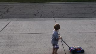 Little Boy Imitates Older Neighbor As He Mows His Lawn - Video