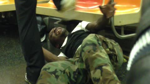 Two men wrestle on the floor with each other on subway train