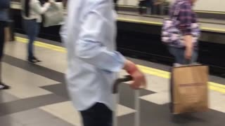 Man in all blue paint waits for subway - Video