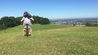 Traildog riding as backpack on mountainbike with owner