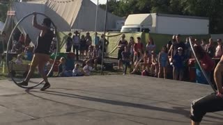 Acrobats ride large hula hoops in Glastonbury - Video