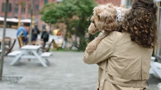 Woman Carrying Her Dog While Walking In The Street