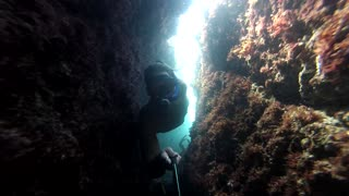 Dangerously tight squeeze diving underneath caves