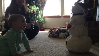 Adorable baby girl sad at melting snowman - Video
