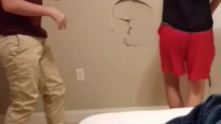 Two guys play wrestling they make a hole in the wall - Video