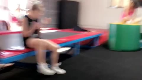 Girl back flips in trampoline folds